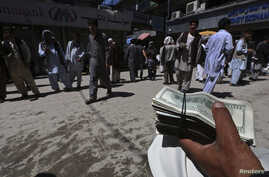 FILE - A money changer holds a stack of U.S. dollars at Kabul's largest money market April 23, 2014.