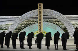 Relatives of victims of the March 11, 2011 earthquake and tsunami bow to the altar as they offer chrysanthemums for the victims at the national memorial service in Tokyo, March 11, 2014.