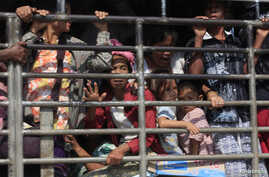 FILE - A group of Myanmar refugees are seen on a pick-up truck in Mae Sot, Thailand.