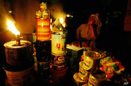 A street vendor sells her wares by the light of a kerosene wick lamp in Lagos, Nigeria, March 1, 2007.
