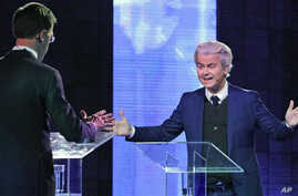 Right-wing populist leader Geert Wilders gestures as he talks to Dutch Prime Minister Mark Rutte, left, during a national televised debate, the first head-to-head meeting of the two political party leaders since the start of the election campaign, at