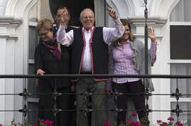 Flanked by his running mates Mercedes Araoz, right, and Martin Vizcarra, presidential candidate Pedro Pablo Kuczynski acknowledges supporters and reporters gathered outside his home in Lima, Peru, Monday, June 6, 2016.