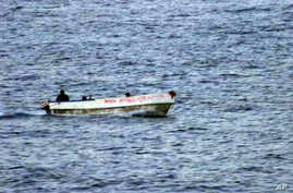 An armed suspected pirate looks over the edge of a skiff, in international waters off the coast of Somalia, (File photo)