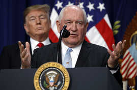 """President Donald Trump listens to Agriculture Secretary Sonny Perdue during a signing ceremony for H.R. 2, the """"Agriculture Improvement Act of 2018,"""" in the Eisenhower Executive Office Building, Dec. 20, 2018, in Washington."""