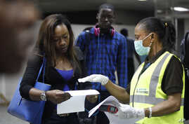 A Nigerian port health official speaks to a passenger arriving at Murtala Muhammed International Airport in Lagos, Nigeria, Aug. 6, 2014.