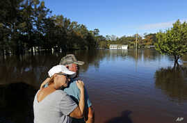 Dianna Wood, embraces her husband Lynn, as they look out over their flooded property as the Little River continues to rise in the aftermath of Hurricane Florence in Linden, North Carolina, Sept. 18, 2018.