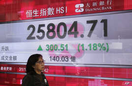 A woman passes an electronic board showing the Hong Kong share index outside a bank in Hong Kong, Dec. 31, 2018.