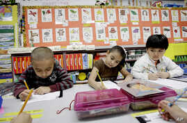 FILE - Kindergarten students work in a bilingual English-Spanish class at school in Texas.