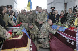 FILE - Ukrainian soldiers pay their respects during a memorial service for comrades Sergiy Baula and Mykola Kuliba, killed in the conflict with pro-Russia separatists in Ukraine's eastern Donetsk region, in Independence Square in Kyiv, Ukraine, May.