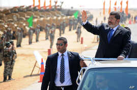 In this image released by the Egyptian Presidency, Egyptian President Mohammed Morsi, waves toward soldiers at a military base in Ismailia, Egypt, Oct. 10, 2012.