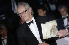 """Director Ken Loach poses for photographers with the Palme d'Or for his film """"I, Daniel Blake"""" during the photo call following the awards ceremony at the 69th international film festival, Cannes, southern France, May 22, 2016."""