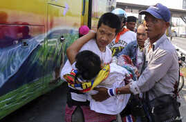Anti-government protesters carry injured protester from a bus to an ambulance after an attack by suspected gunmen while on their way back from a protest in Bangkok, Thailand, April 1, 2014.