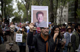 A man holds up a photo of Mexican journalist Miroslava Breach, gunned down in the northern state of Chihuahua on Thursday, during a march in Mexico City, March 25, 2017.