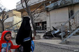 A Syrian woman and child walk past the shuttered doors of a restaurant which was the site of a suicide attack targeting US-led coalition forces in the  northern Syrian city of Manbij which killed four US servicemen the previous day on Jan. 17, 2019.