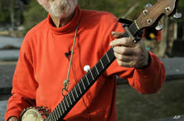 FILE - Folk singer Pete Seeger plays his banjo in Beacon, New York, May 5, 2006.