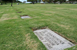 FILE - A gravestone marking 12 sets of unidentified remains from the USS Oklahoma buried at the National Memorial Cemetery of the Pacific in Honolulu.
