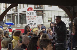 Protesters gather during a rally outside an Immigration and Customs Enforcement office in Portland, Oreron. Federal immigration officers stopped two vans carrying 19 workers headed to a forest in Oregon to pick an ornamental shrub and took 10 of them