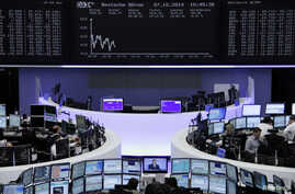Traders at their desks at the Frankfurt stock exchange, Oct. 7, 2014. While stock market prices have risen, other investments have been subdued, according to the International Monetary Fund (IMF).