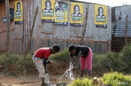 Children collect water from a communal tap beneath election posters for President Jacob Zuma's African National Congress (ANC) in Bekkersdal township south of Johannesburg, May 3, 2014. Bekkersdal is one of many townships that have seen violent servi