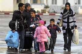 Members of a Tunisian family carry their belongings after they fled from Libya, at the Tunisia-Libya border near the village of Ras Ajdir, Tunisia, Wednesday, Feb. 23, 2011