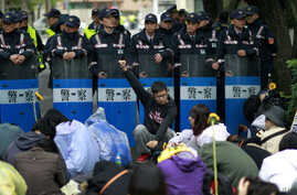 Students protesting against a China Taiwan trade pact rally in front of a wall of police outside of the occupied legislature, in Taipei, Taiwan, Thursday, March 20, 2014. Hundreds of opponents of a trade pact with China continued to demonstrate in an