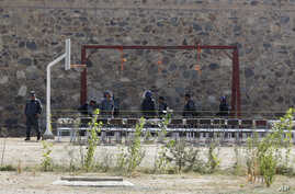 Afghanistan's police officers take positions by nooses prepared to execute men at a jail in Kabul, Afghanistan, Oct. 8, 2014.