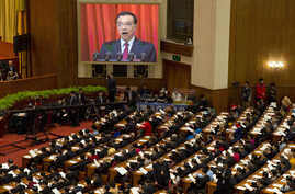 Chinese Premier Li Keqiang is displayed on a huge screen as he delivers a work report at the opening session of the annual National People's Congress at Beijing's Great Hall of the People, March 5, 2017.