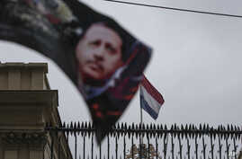 A banner with a picture of Turkish President Recep Tayyip Erdogan, is waved by protesters outside the Dutch consulate in Istanbul, March 12, 2017.