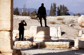 A Syrian army soldier takes a picture of a fellow soldier standing on ruins in the historic city of Palmyra, Syria, March 4, 2017.