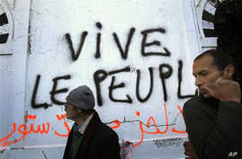 """Graffiti in Tunis reading """"Long live the people"""" left by protesters demanding that any future government be free of holdovers from the former president's regime, 23 Jan 2011"""