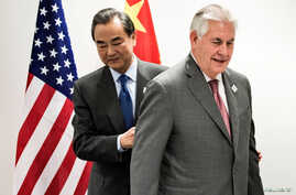 Secretary of State Rex Tillerson, right, and China's Foreign Minister Wang Yi walk to their seats before a meeting on the sidelines of a gathering of Foreign Ministers of the G20 in Bonn, Germany, Feb. 17, 2017.