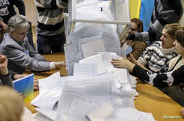 Members of a local electoral commission empty a ballot box at a polling station after voting day in Kiev, October 26, 2014. Ukrainian President Petro Poroshenko hailed a sweeping victory for pro-Europe parties in an election on Sunday, saying the vot...