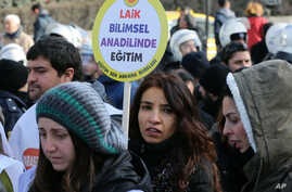 """FILE - A woman holds a placard demanding """"a secular and science-based education system"""" as hundreds of students and teachers march at a rally in Ankara, Feb. 13, 2015."""