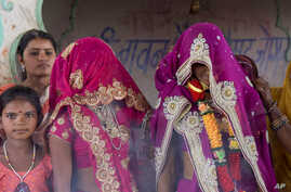 FILE - An underage bride, right, stands with family members during her marriage at a Hindu temple near Rajgarh, Madhya Pradesh state, India, April 17, 2017.