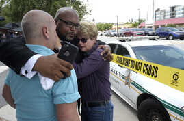 Terry DeCarlo, executive director of the LGBT Center of Central Florida, left, Kelvin Cobaris, pastor of The Impact Church, center, and Orlando City Commissioner Patty Sheehan console each other after a shooting involving multiple fatalities at a nig