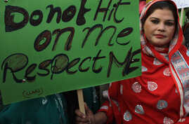 FILE - Pakistani woman holds a sign as she observes the International Day for the Elimination of Violence against Women, in Lahore, Pakistan, Nov. 25, 2015.