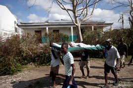 Men carry a woman wounded in Hurricane Matthew in Chantal, Haiti, Oct. 7, 2016.