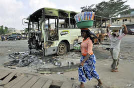 Women carrying loads on their heads walk past a burnt-out bus in Abobo, an Alassane Ouattara stronghold in Abidjan, February 8, 2011