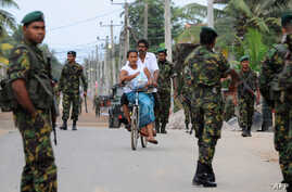 A Sri Lankan resident rides a bicycle along a road as Special Task Force (STF) soldiers patrol following clashes between Muslims and an extremist Buddhist group in the town of Alutgama, June 16, 2014.
