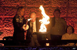 Holocaust survivor Robert Tomashof and his daughter Rutti Tomashof light a torch during the opening ceremony of the Holocaust Remembrance Day at the Yad Vashem Holocaust Memorial in Jerusalem, May 4, 2016.