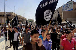 Demonstrators chant pro-al-Qaida-inspired Islamic State of Iraq and the Levant (ISIL) as they carry al-Qaida flags in front of the provincial government headquarters in Mosul, 225 miles (360 kilometers) northwest of Baghdad, Iraq, June 16, 2014.