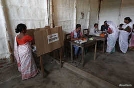 A woman (L) casts her vote with an electronic voting machine as others get their voting slip from an officer at a polling station in Majuli, a large river island in the Brahmaputra river, Jorhat district, in the northeastern Indian state of Assam, Ap