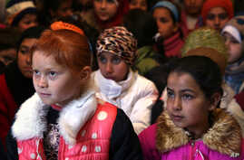 FILE - In this Wednesday, Jan. 27, 2016 file photo, Syrian refugee children sit on the ground as they listen to their teacher inside a tent, home for a refugee family that has been turned into a makeshift school, in a Syrian refugee camp in the easte