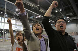 Radical activist candidates from Youngspiration group, from left, Yau Wai-ching, Kenny Wong and Henry Wong shout slogans as they celebrate after Yau won the legislative council election in Hong Kong, Monday, Sept. 5, 2016.