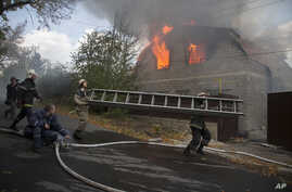 Firefighters try to extinguish a burning private house after shelling in the town of Donetsk, eastern Ukraine, Oct. 5, 2014.