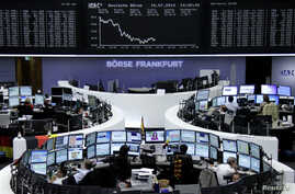 Traders are seen at their desks in front of the DAX board at the Frankfurt stock exchange, Germany, July 10, 2014.