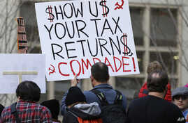 "Tax FILE - A woman in Seattle holds a sign during a rally that reads ""Show us your tax returns, Comrade"" in reference to calls for President Donald Trump to release his tax returns and his alleged ties to Russia, April 15, 2017."