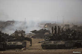 Israeli soldiers stand atop a tank at a staging area near the border with the Gaza Strip, July 13, 2014.