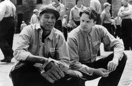 """In this photo provided by Courtesy Castle Rock Entertainment via the Library of Congress, inmates Red (Morgan Freeman), left, and Andy (Tim Robbins) share a quiet moment in the prison yard in a scene from """"The Shawshank Redemption."""""""