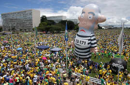 Demonstrators demand the impeachment of Brazil's President Dilma Rousseff during a rally where a large inflatable doll of former President Luiz Inacio Lula da Silva stands in prison garb in Brasilia, Brazil, Sunday, March 13, 2016.